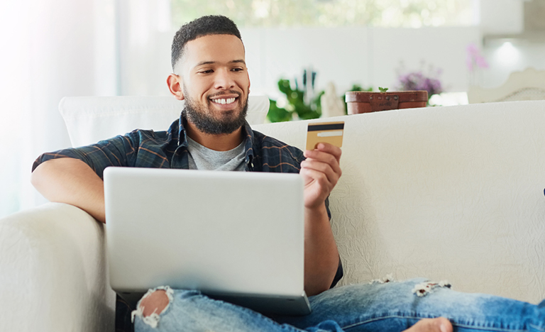 Man looking at credit card while on computer.